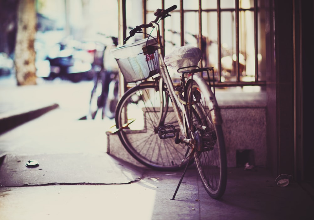 gray bicycle parked near store