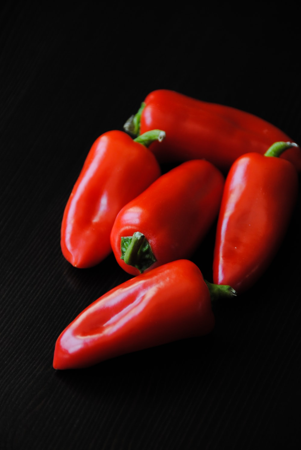 five red bell peppers on black textile