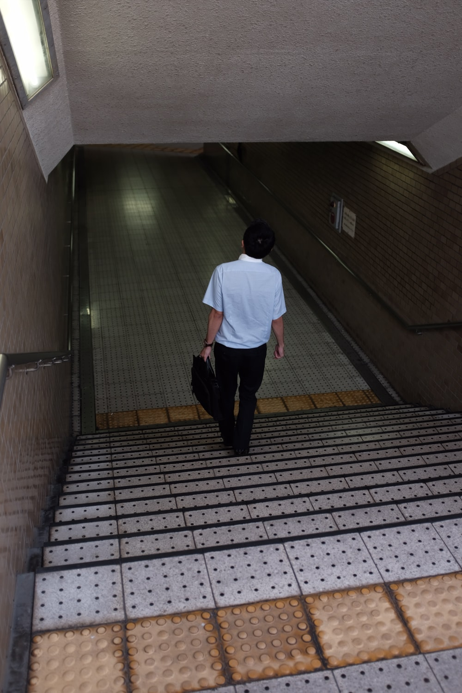 man holding bag walking down stairs