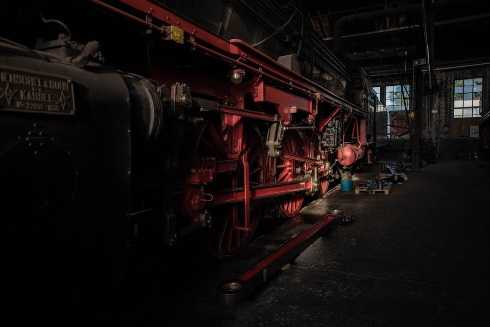 red and black train inside warehouse