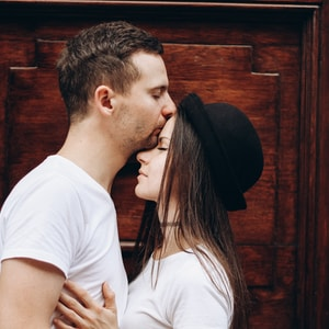 man kissing woman forehead