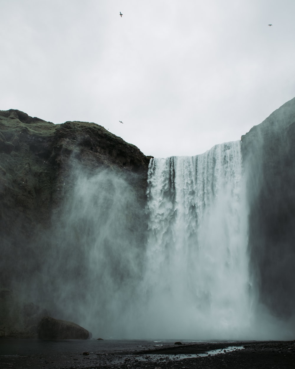 waterfall under white clouds