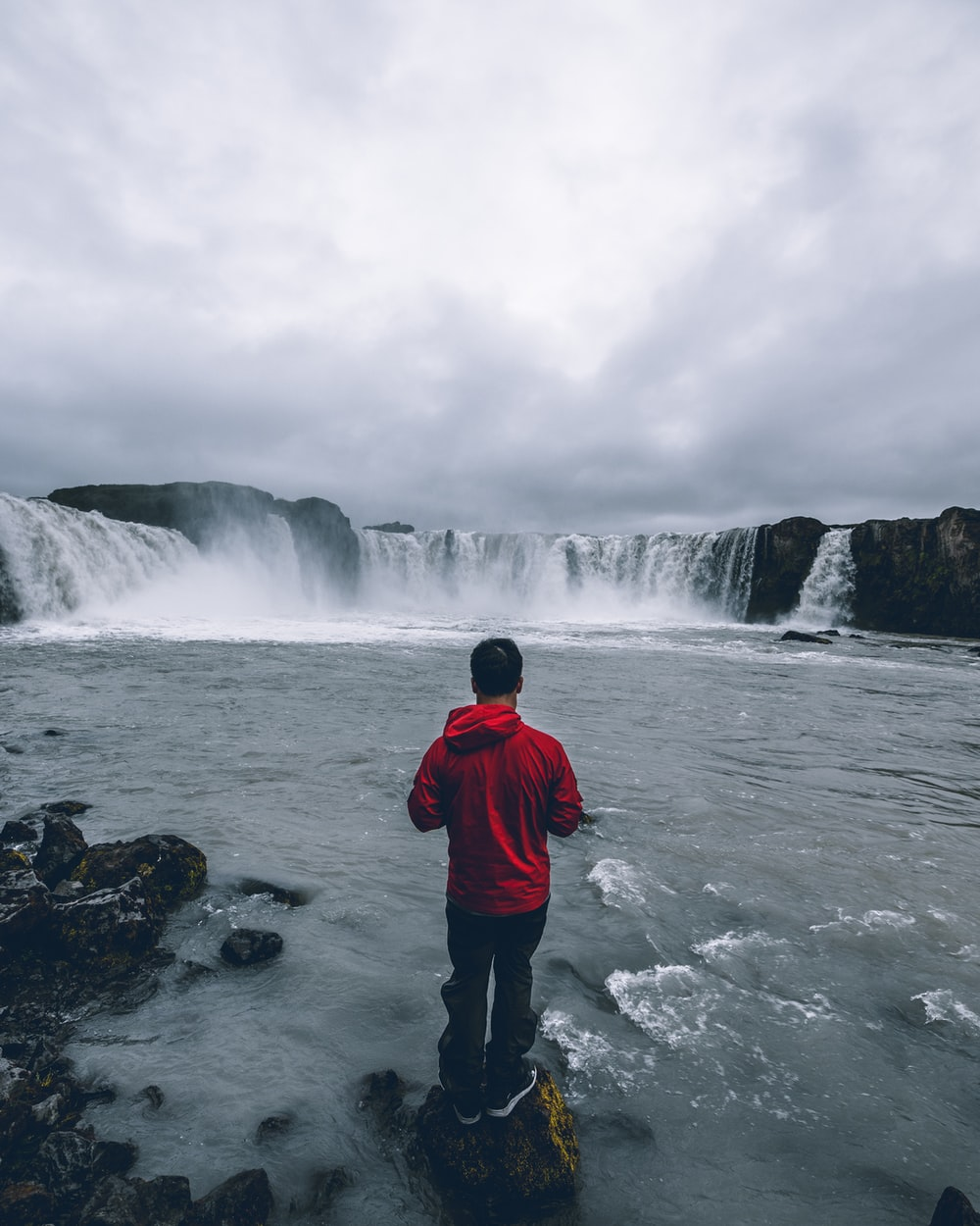 person standing in a rock near waterfalls during daytime