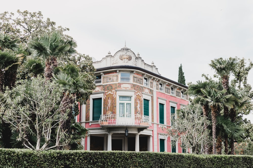white, beige, and pink building near trees