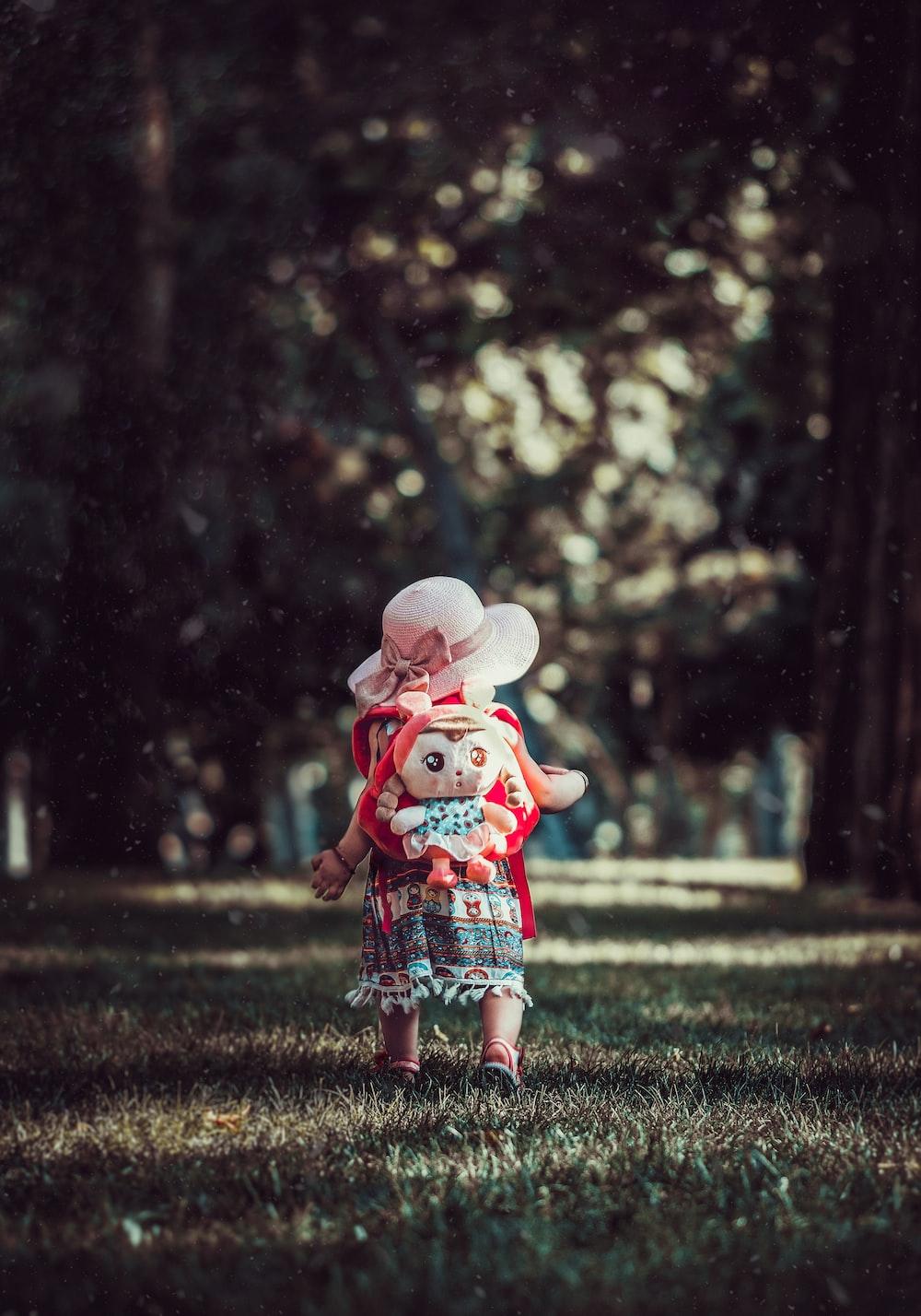 toddler wearing backpack walking near trees