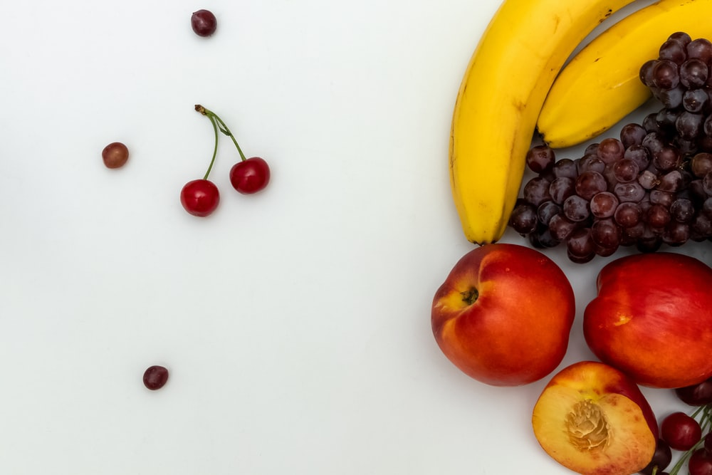 ripe banana, apple, grapes, and cherries fruits