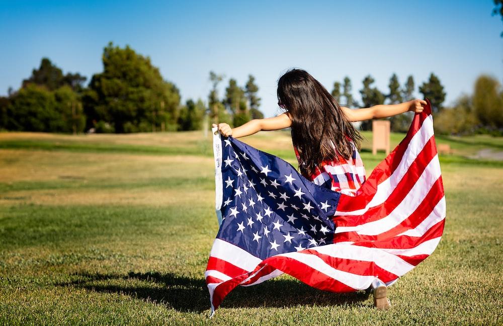 girl holding US flag on grassland