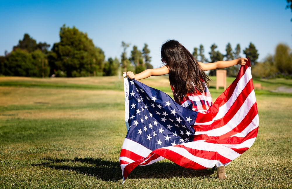 girl holding US flag on grassland