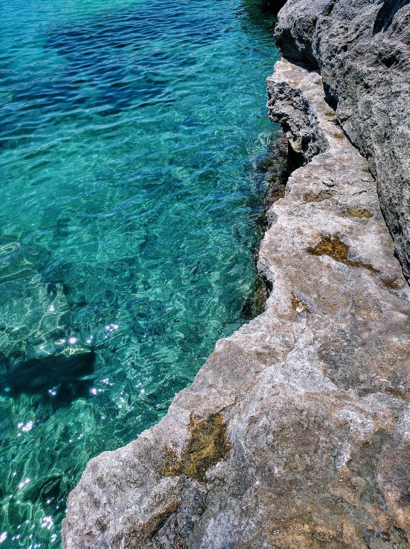 body of water beside gray rock