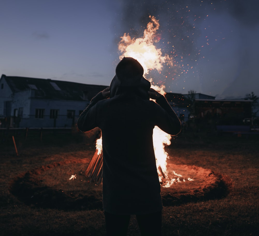 person standing in front of bonfire