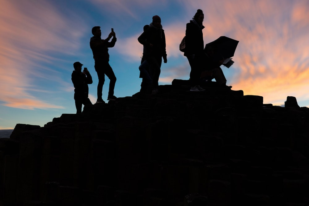 silhouette of people standing on top of mountain during sunset