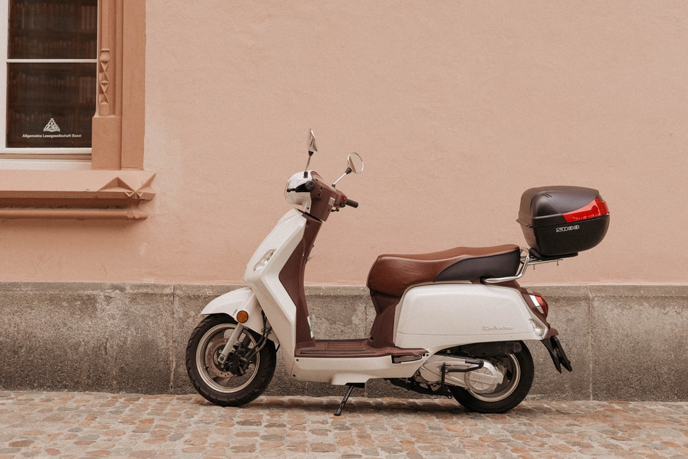 brown and white motor scooter near wall