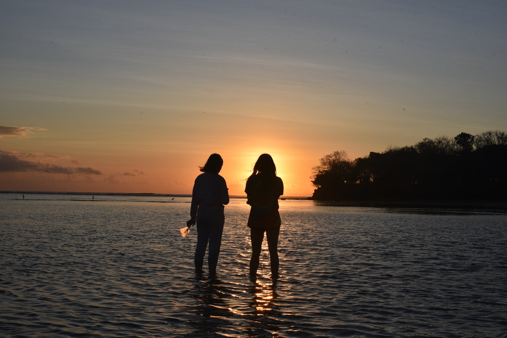 two women standing on the surface of water during daytime