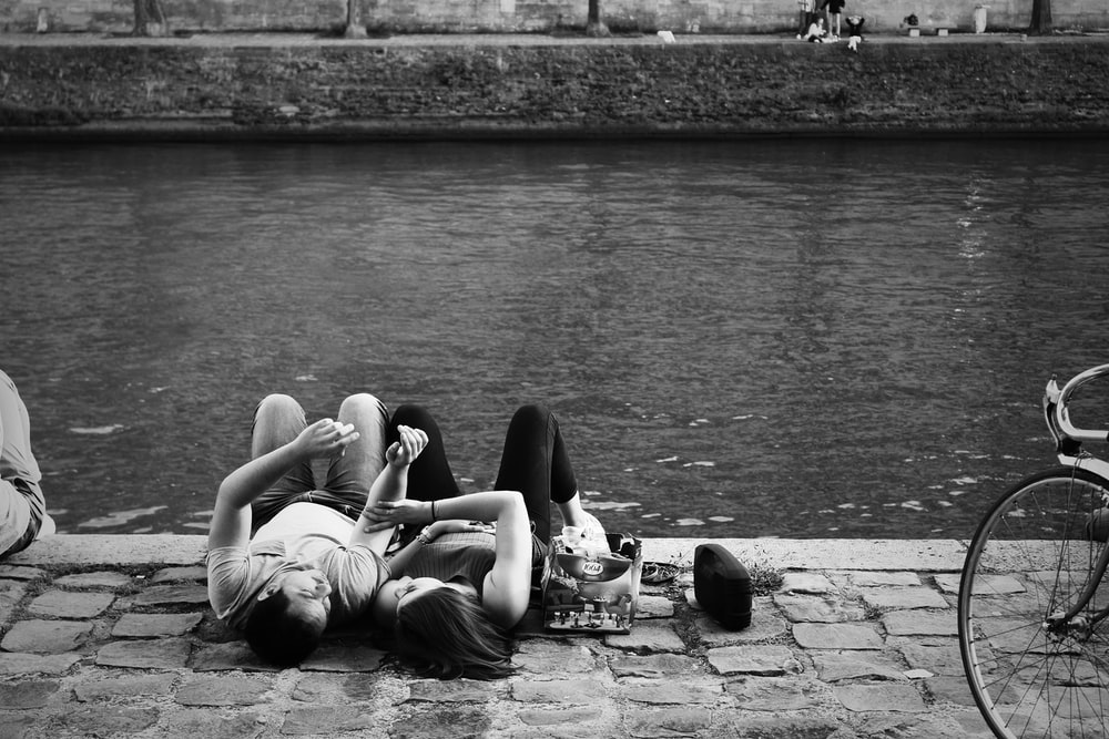 man and woman lying on ground near body of water