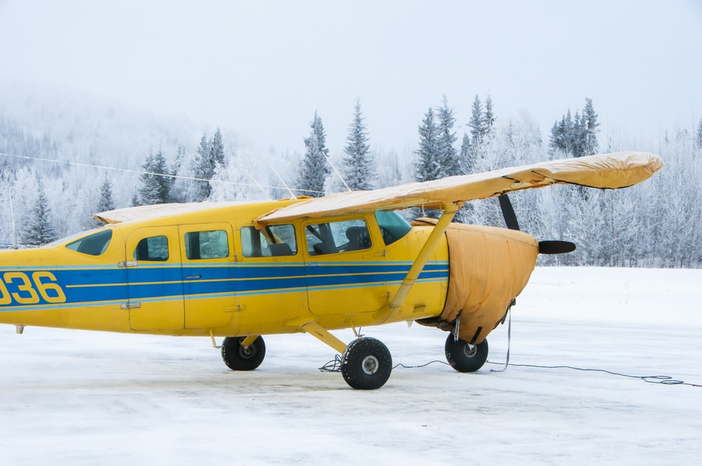 yellow monoplane on snow field