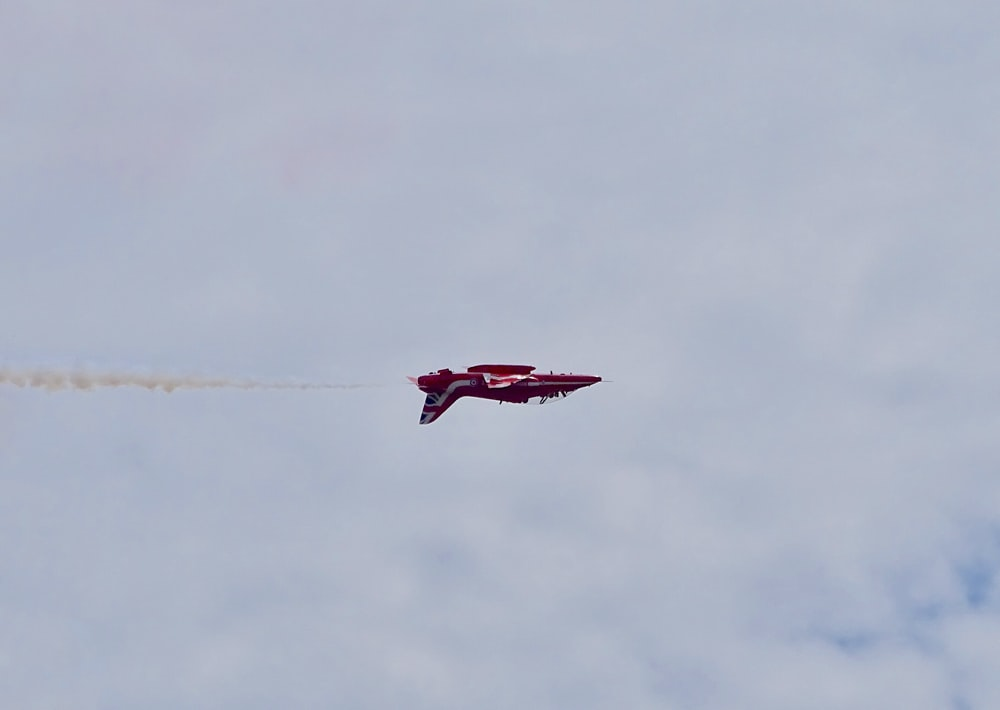 red airplane flying under cloudy sky during daytime