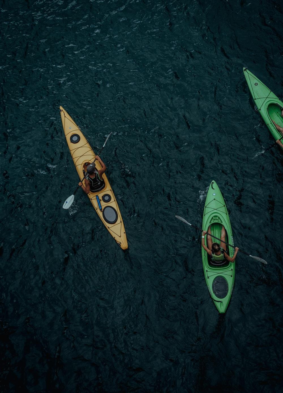 three people kayaking on body of water