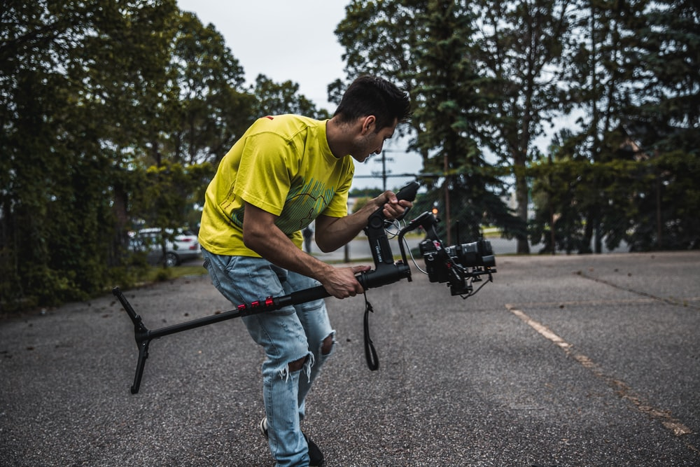 man wearing yellow shirt holding camera