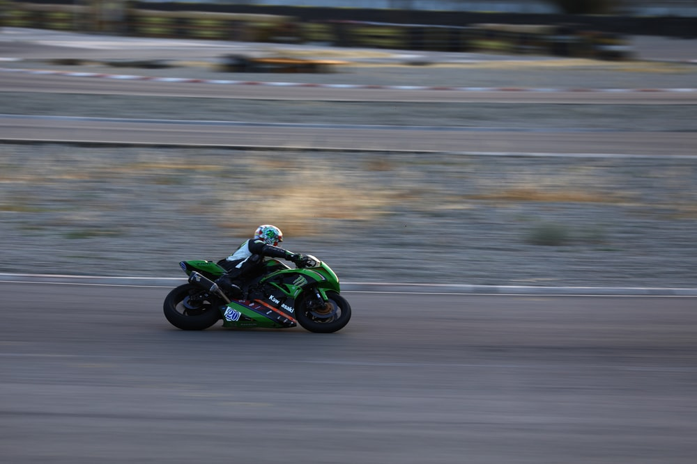 person riding green and black sportsbike