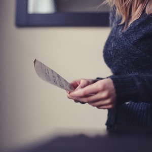 women wearing a black sweater holding a paper close-up photography