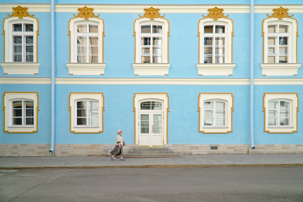 women walking near a blue wall building during daytime