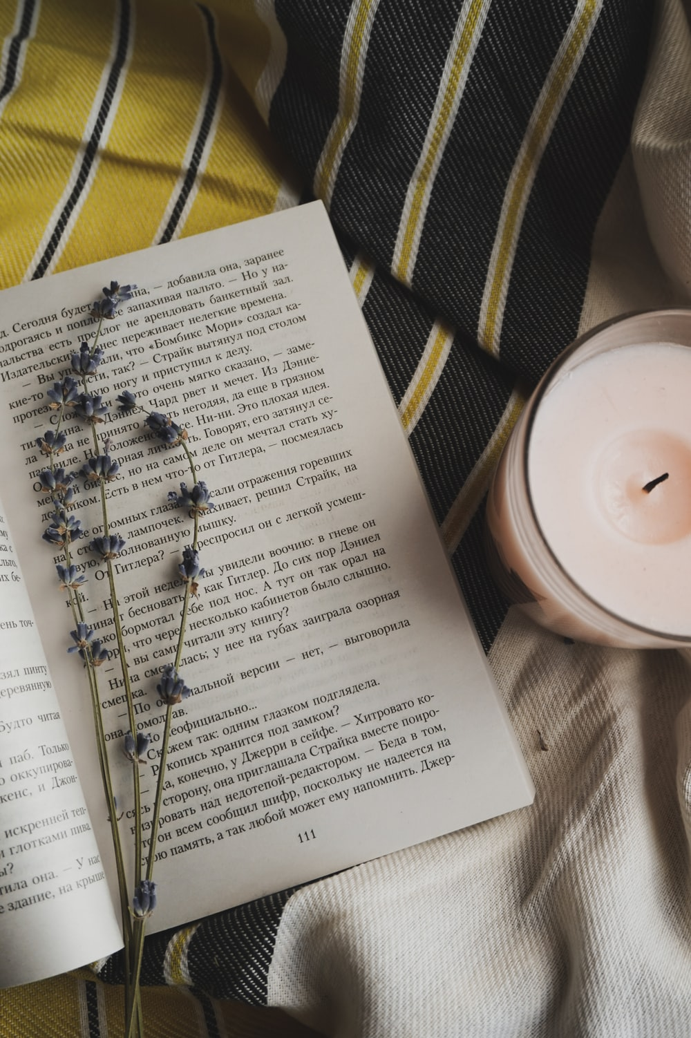 flowers on open book beside votive candle
