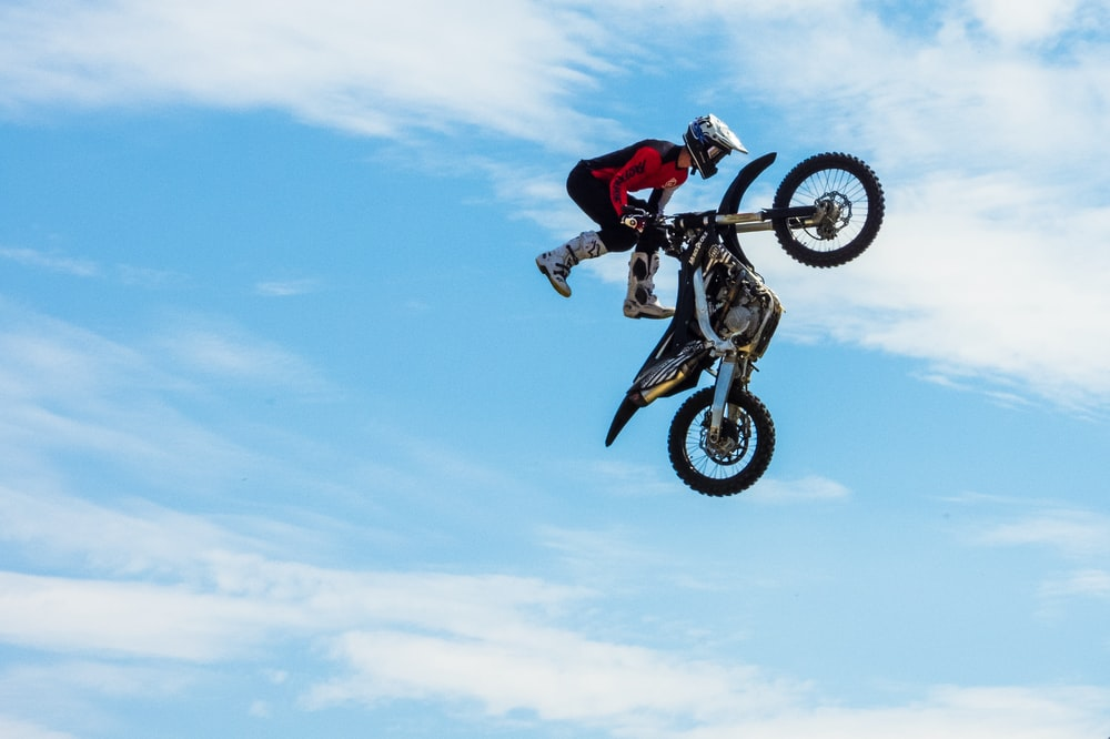 person wearing red and black jacket while holding motocross dirt bike