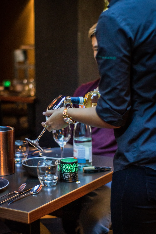 person putting wine in wine glass