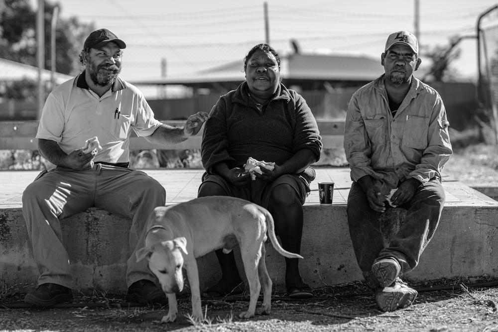greyscale photo of men sitting on concrete block