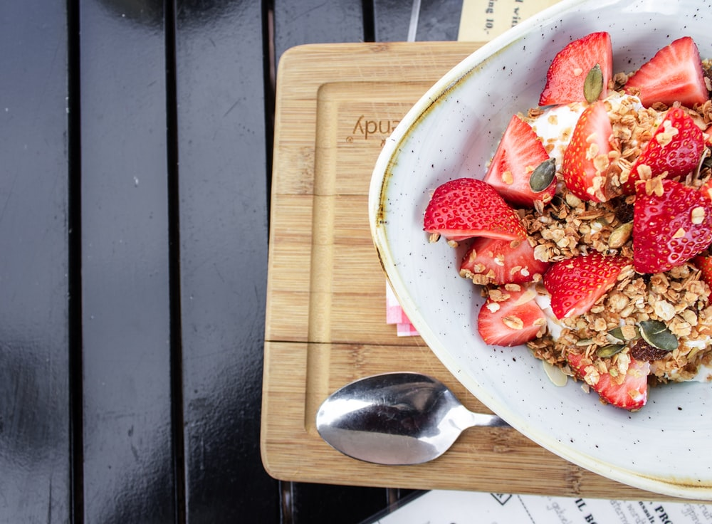 sliced strawberries in white ceramic bowl