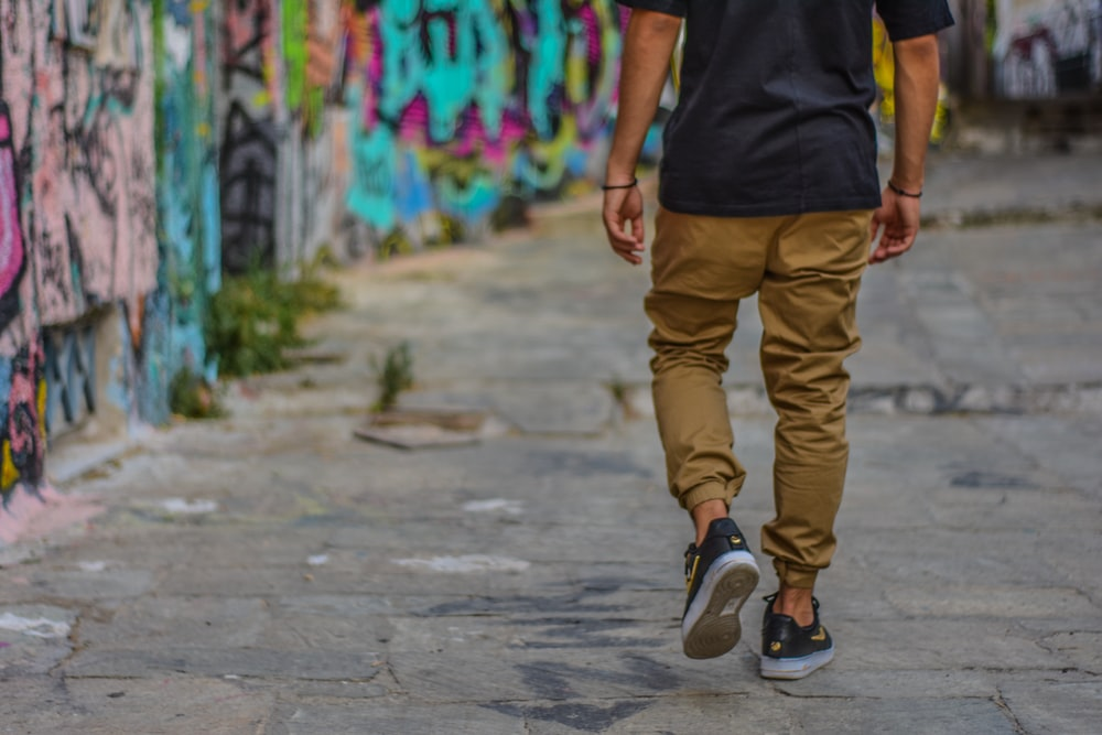 man wearing black shirt and brown pants walking beside wall with graffiti
