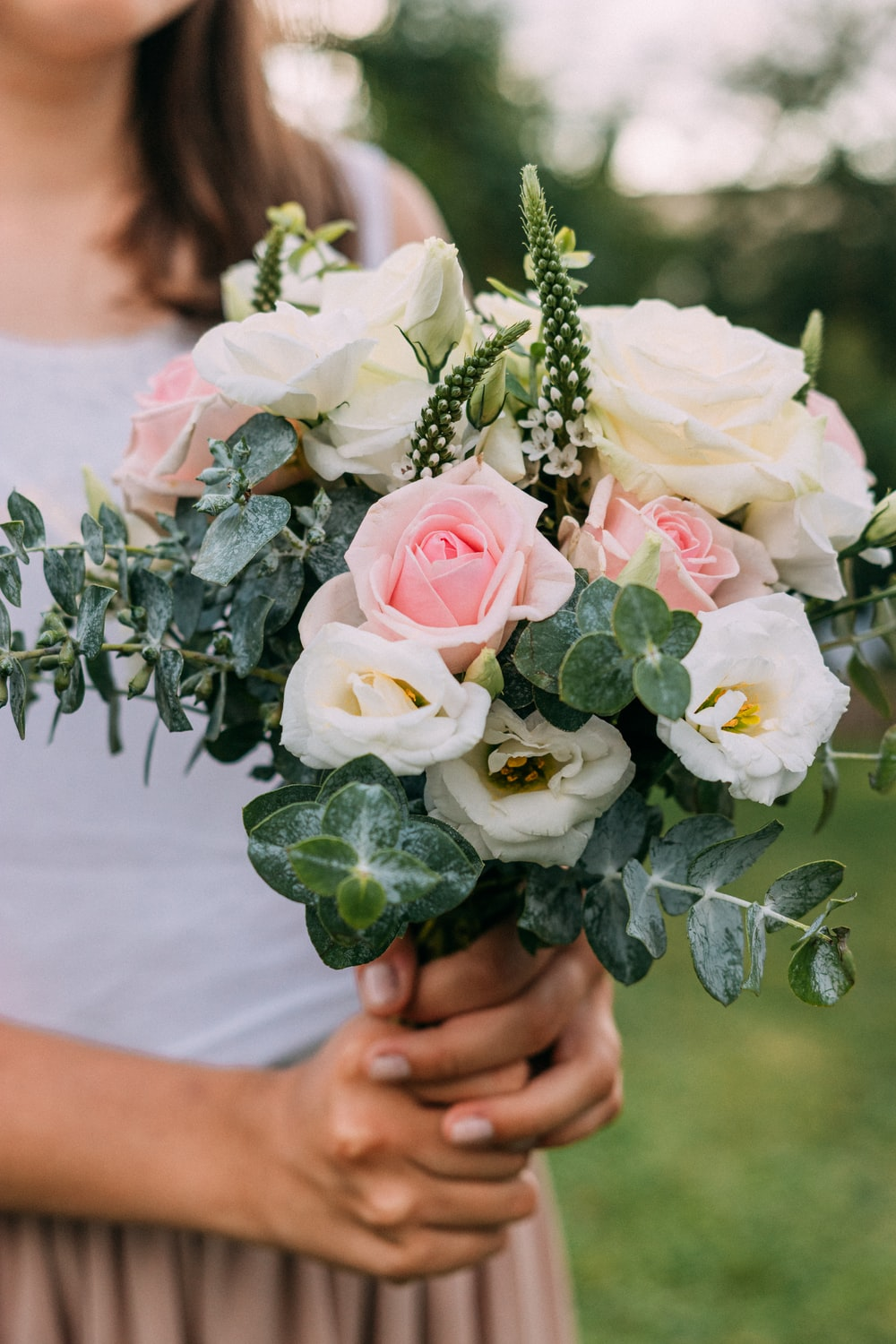 woman holding white and pink rose bouquet