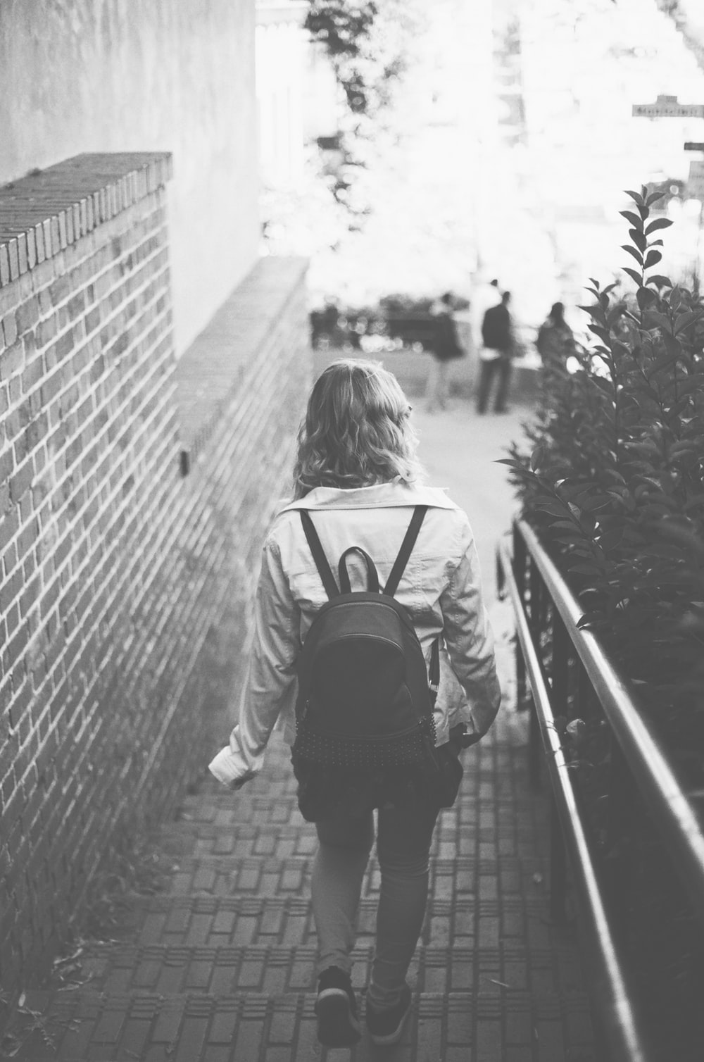grayscale photography of woman with backpack