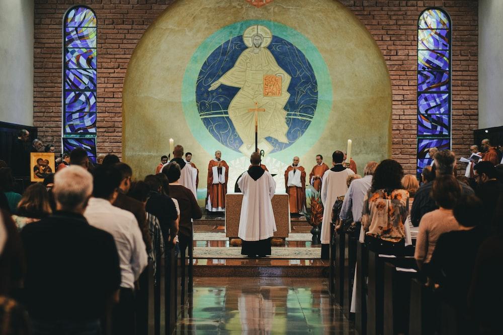 priest beside people in church