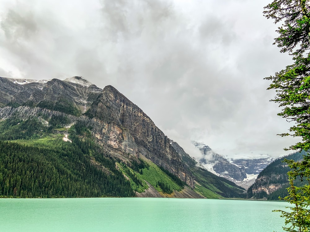 lake surrounded by mountain during aytime