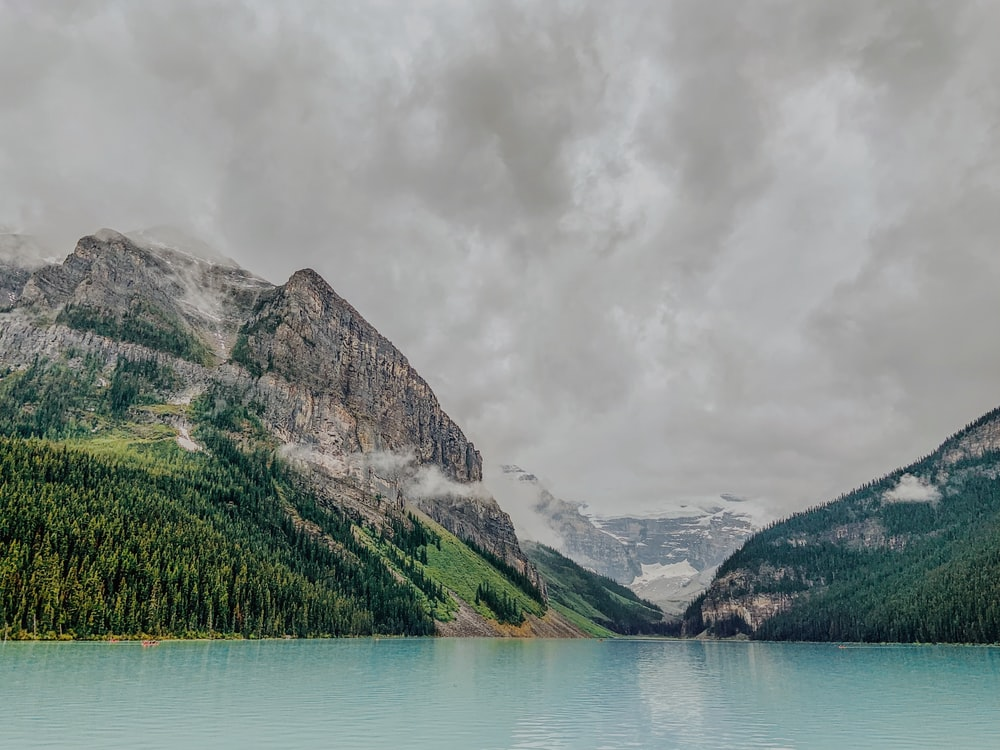 body of water in front of mountain under cloudy sky