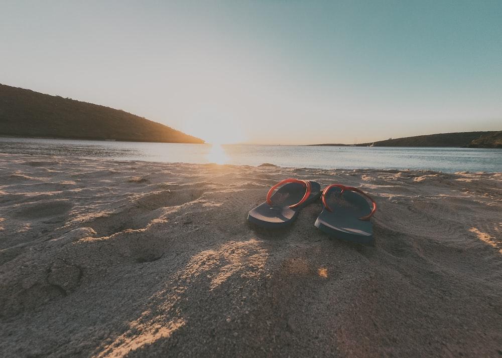 pair of blue flip-flops on seashore