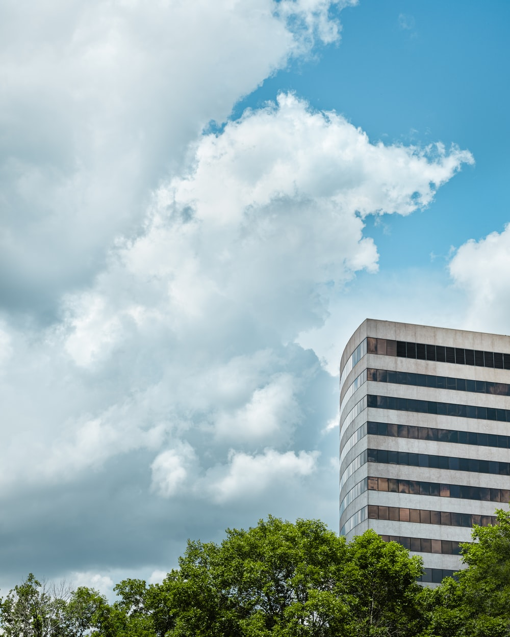 white concrete multi-storey building under cloudy sky during daytime