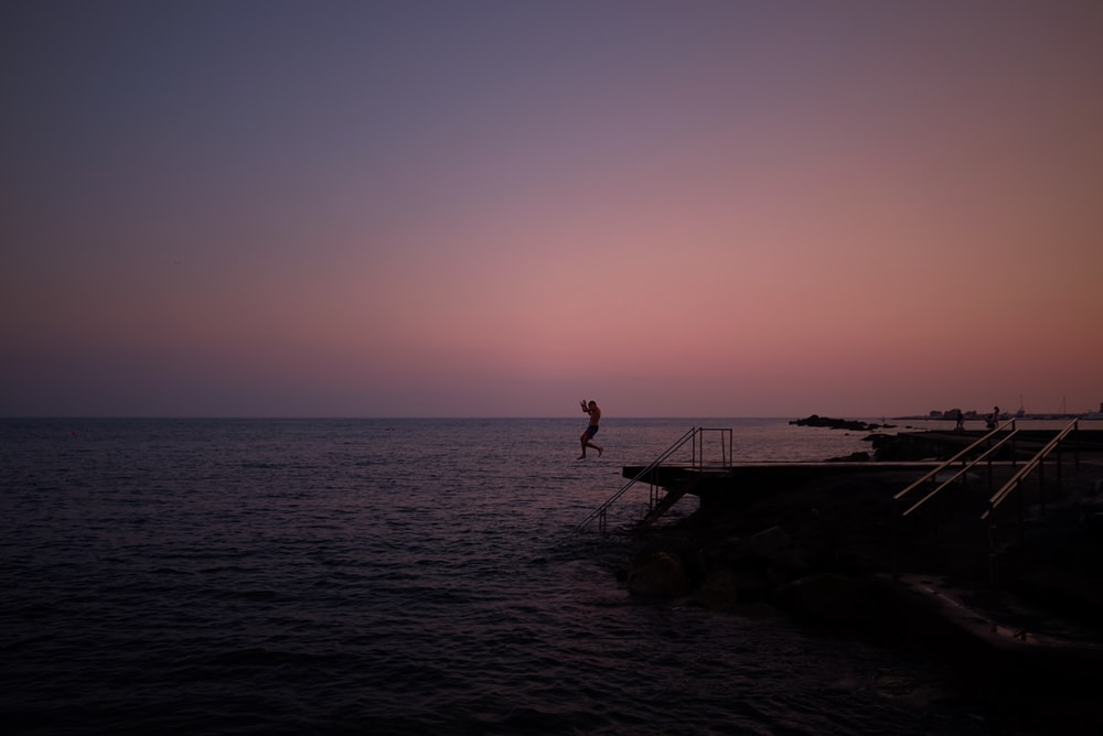 person diving in the sea from a platform