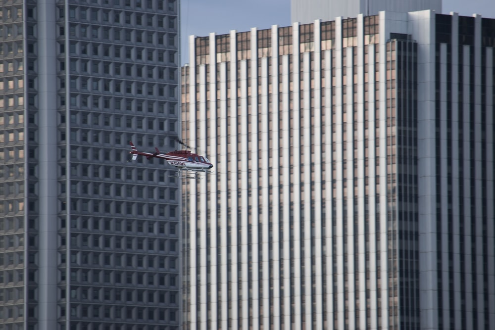 red an white helicopter flying around the building