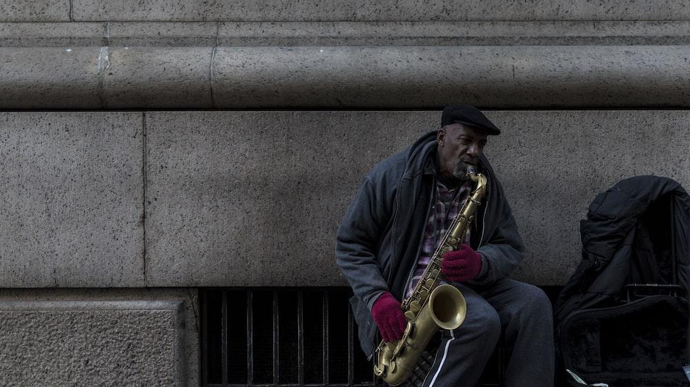 man in black hoodie playing saxophone
