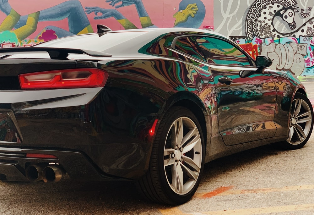 black Chevrolet Camaro coupe near painted wall
