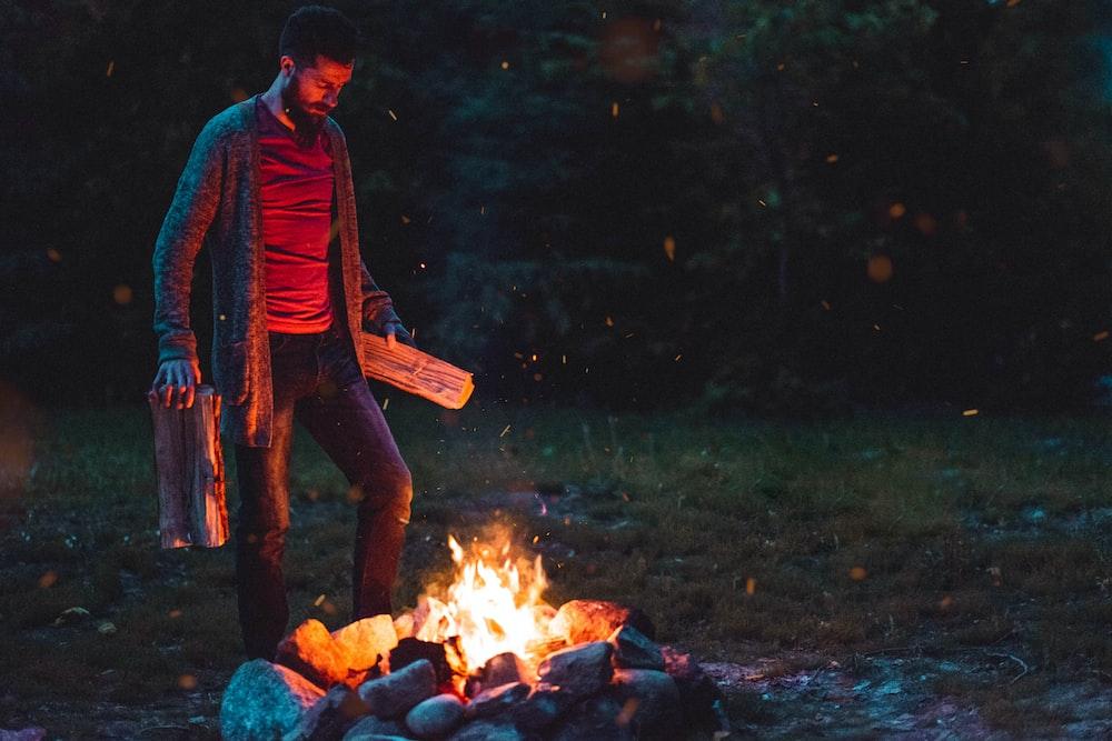 man standing near bonfire
