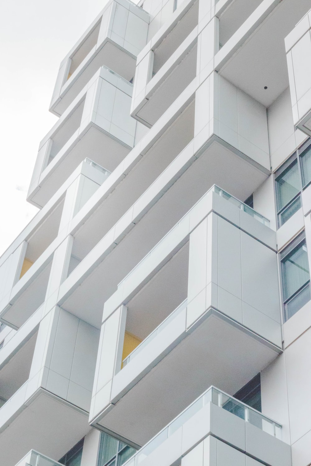 low-angle photography of white concrete multi-storey building
