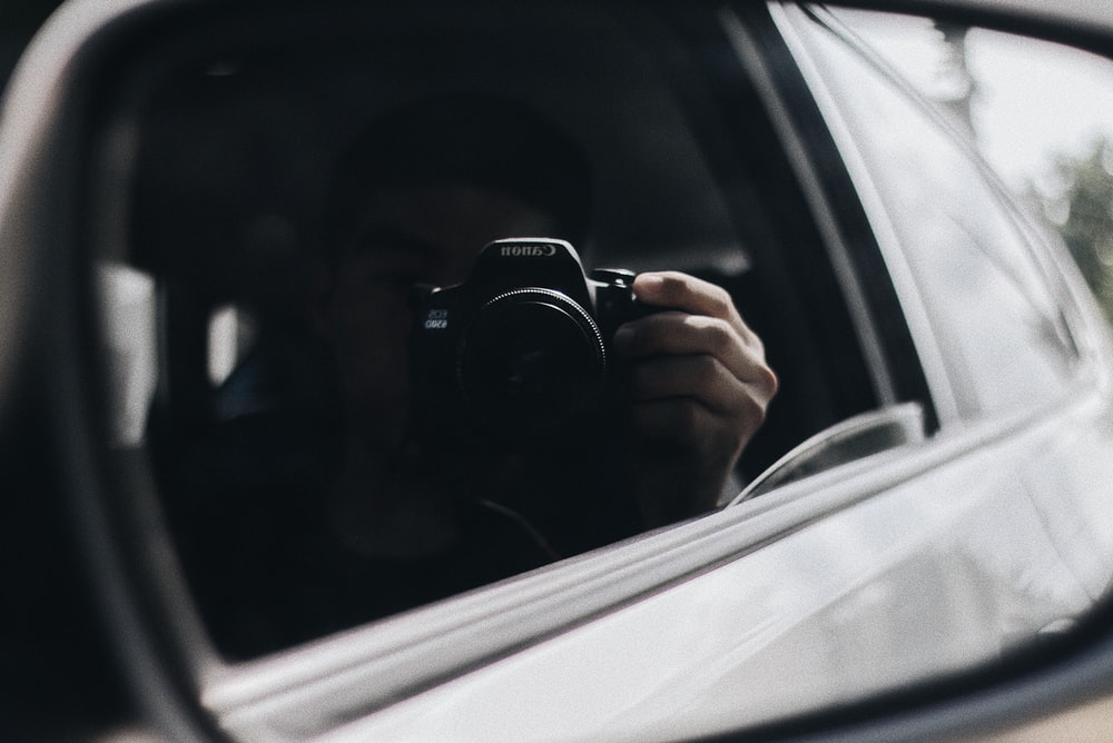 reflection of person holding camera on side mirror