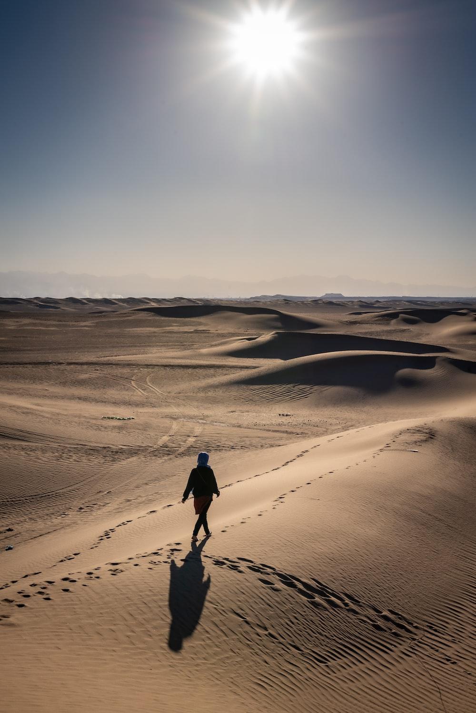 person walking on desert under clear blue sky