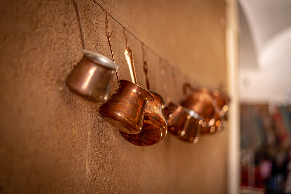 brass-colored cook ware hangs on wall