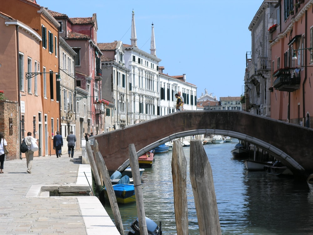 people walking on bridge and near water canal