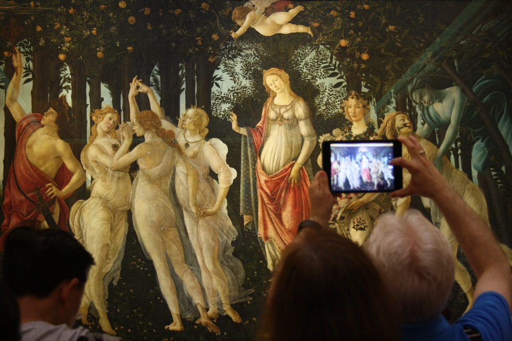 person taking a picture of a dancing women and men painting