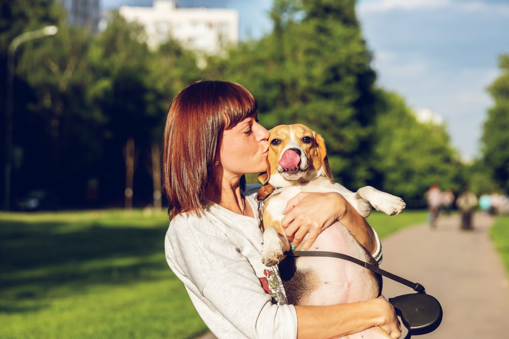 woman carrying and kissing dog